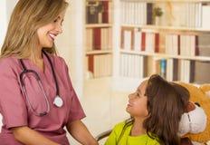 Όμορφος γιατρός που μιλά με ένα παιδί σε ένα νοσοκομείο, που φορά ένα στηθοσκόπιο γύρω από το λαιμό της, σε ένα υπόβαθρο γραφείων Στοκ φωτογραφία με δικαίωμα ελεύθερης χρήσης