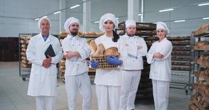 Όμορφος γυναικείος αρτοποιός βιομηχανίας τροφίμων και η κύρια ομάδα συναδέλφων της που φαίνονται ευθείς στη κάμερα και το χαμόγελ φιλμ μικρού μήκους