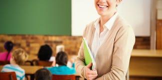 Όμορφος δάσκαλος που χαμογελά στη κάμερα στο πίσω μέρος της τάξης Στοκ φωτογραφίες με δικαίωμα ελεύθερης χρήσης