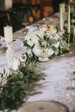 Όμορφος διακοσμημένος γαμήλιος πίνακας με τις floral άσπρες ανθοδέσμες, τα κηροπήγια και ένα άσπρο τραπεζομάντιλο Στοκ εικόνα με δικαίωμα ελεύθερης χρήσης