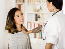 Όμορφος διαστισμένος νέος γιατρός που χρησιμοποιεί το χέρι της που ελέγχει το στήθος του ασθενή, στο υπόβαθρο γραφείων Στοκ Φωτογραφίες