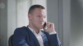 Όμορφος διευθυντής γραφείων που μιλά στο κινητό τηλέφωνο με τη φίλη του φιλμ μικρού μήκους
