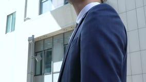Όμορφος διευθυντής γραφείων στο επιχειρησιακό κοστούμι που εξετάζει το κτίριο γραφείων, απασχόληση φιλμ μικρού μήκους