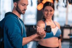 Όμορφος εκπαιδευτής που διδάσκει την παχύσαρκη γυναίκα που χρησιμοποιεί barbells στοκ εικόνα με δικαίωμα ελεύθερης χρήσης