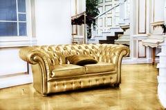 Όμορφος εκλεκτής ποιότητας χρυσός καναπές δίπλα στον τοίχο (illustrati αναδρομικός-ύφους στοκ εικόνες