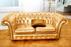 Όμορφος εκλεκτής ποιότητας χρυσός καναπές δίπλα στον τοίχο (illustrati αναδρομικός-ύφους στοκ φωτογραφία με δικαίωμα ελεύθερης χρήσης
