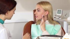 Όμορφος επισκεπτόμενος οδοντίατρος γυναικών με το πονώντας δόντι απόθεμα βίντεο