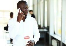 Όμορφος επιχειρηματίας αφροαμερικάνων που μιλά στο κινητό τηλέφωνο στην αρχή Στοκ φωτογραφία με δικαίωμα ελεύθερης χρήσης