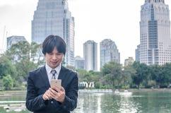 Όμορφος επιχειρηματίας που ελέγχει τα ηλεκτρονικά ταχυδρομεία στο τηλέφωνο Στοκ φωτογραφία με δικαίωμα ελεύθερης χρήσης