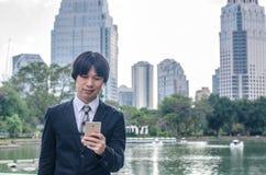 Όμορφος επιχειρηματίας που ελέγχει τα ηλεκτρονικά ταχυδρομεία στο τηλέφωνο Στοκ Φωτογραφία