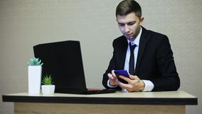 Όμορφος επιχειρηματίας που εργάζεται στο γραφείο, που δακτυλογραφεί σε ένα lap-top φιλμ μικρού μήκους