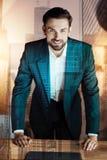 Όμορφος επιχειρηματίας που κλίνει στον πίνακα στο γραφείο του Στοκ Φωτογραφίες