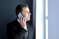 Όμορφος επιχειρηματίας που μιλά στο κινητό τηλέφωνο στο σύγχρονο γραφείο Στοκ φωτογραφίες με δικαίωμα ελεύθερης χρήσης
