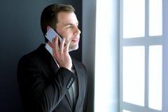 Όμορφος επιχειρηματίας που μιλά στο κινητό τηλέφωνο στο σύγχρονο γραφείο Στοκ Εικόνες