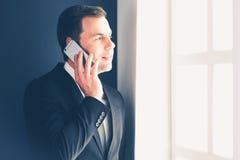 Όμορφος επιχειρηματίας που μιλά στο κινητό τηλέφωνο στο σύγχρονο γραφείο Στοκ φωτογραφία με δικαίωμα ελεύθερης χρήσης