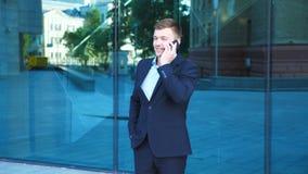 Όμορφος επιχειρηματίας που μιλά στο τηλέφωνο κοντά στο γραφείο και το επίτευγμα εορτασμού Το νέο επιχειρησιακό άτομο άκουσε τις κ απόθεμα βίντεο