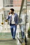 Όμορφος επιχειρηματίας που μιλά στο τηλέφωνο στην αρχή Στοκ φωτογραφία με δικαίωμα ελεύθερης χρήσης