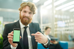 Όμορφος επιχειρηματίας που παρουσιάζει κινητό App Στοκ φωτογραφία με δικαίωμα ελεύθερης χρήσης