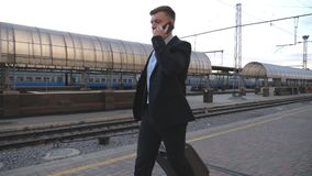 Όμορφος επιχειρηματίας που περπατά μέσω του σιδηροδρομικού σταθμού με τις αποσκευές του και που μιλά στο τηλέφωνο Νέο επιχειρησια απόθεμα βίντεο
