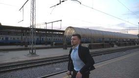Όμορφος επιχειρηματίας που τρέχει μέσω του σιδηροδρομικού σταθμού που πιέζει χρονικά στο τραίνο Επιτυχές επιχειρησιακών προσώπων  απόθεμα βίντεο