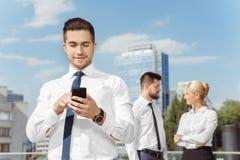 Όμορφος επιχειρηματίας που χρησιμοποιεί το τηλέφωνό του υπαίθριο Στοκ φωτογραφία με δικαίωμα ελεύθερης χρήσης