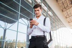 Όμορφος επιχειρηματίας που χρησιμοποιεί το smartphone κοντά στο κτίριο γραφείων Στοκ εικόνα με δικαίωμα ελεύθερης χρήσης