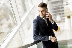 Όμορφος επιχειρηματίας που χρησιμοποιεί το smartphone στο γραφείο Στοκ Φωτογραφία