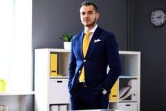 Όμορφος επιχειρηματίας στο κοστούμι που εξετάζει τη κάμερα Στοκ Φωτογραφία