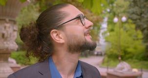 Όμορφος επιχειρηματίας hipster eyeglasses με το ponytail που κοιτάζει γύρω από την ύπαρξη θετικός και κατάπληκτος στο πάρκο φιλμ μικρού μήκους