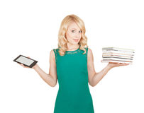 Όμορφος, λεπτός ξανθός συγκρίνει μια ταμπλέτα και τα βιβλία Στοκ Φωτογραφία