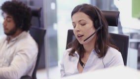 Όμορφος εργαζόμενος γραφείων στο τηλέφωνο στο κέντρο κλήσης απόθεμα βίντεο