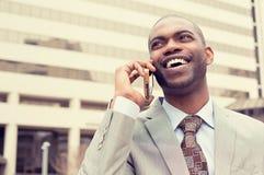 Όμορφος ευτυχής γελώντας νέος επιχειρηματίας που μιλά στο κινητό τηλέφωνο Στοκ Εικόνες