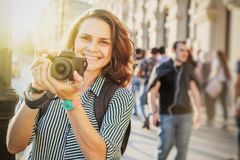 Όμορφος ευτυχής χαμογελώντας ταξιδιώτης γυναικών γυναικών με τη κάμερα διαθέσιμη Στοκ φωτογραφία με δικαίωμα ελεύθερης χρήσης