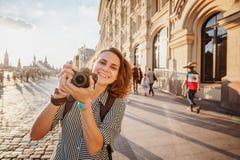 Όμορφος ευτυχής χαμογελώντας ταξιδιώτης γυναικών γυναικών με τη κάμερα διαθέσιμη Στοκ Φωτογραφίες