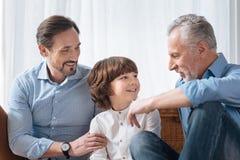 Όμορφος ευχαριστημένος παππούς που εξετάζει τον εγγονό του στοκ εικόνες