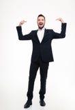 Όμορφος εύθυμος επιχειρηματίας στο κοστούμι που γελά και που δείχνει σε τον Στοκ Εικόνες