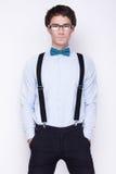 Όμορφος εύθυμος νεαρός άνδρας που φορά τα γυαλιά, το πουκάμισο με suspenders και μια πεταλούδα στο λαιμό του συναισθηματικοί άνθρ Στοκ φωτογραφία με δικαίωμα ελεύθερης χρήσης