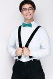 Όμορφος εύθυμος νεαρός άνδρας που φορά τα γυαλιά, το πουκάμισο με suspenders και μια πεταλούδα στο λαιμό του συναισθηματικοί άνθρ Στοκ Εικόνες
