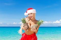 Όμορφος εύθυμος ξανθός στο καπέλο Χριστουγέννων και φούστα που κρατά ένα π Στοκ Εικόνες