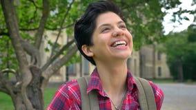 Όμορφος εύθυμος φοιτητής πανεπιστημίου με τη μαύρη κοντή τρίχα που γελά και που χαμογελά στη κάμερα, που στέκεται στο πάρκο πλησί φιλμ μικρού μήκους