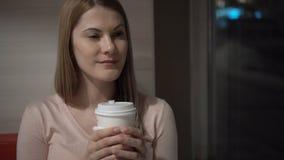 Όμορφος ελκυστικός νέος καφές κατανάλωσης γυναικών σε έναν καφέ Νύχτα βραδιού Κόκκινος καναπές φλυτζανιών καφέ εγγράφου απόθεμα βίντεο