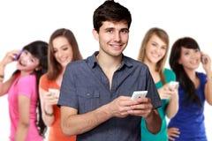 Όμορφος ελκυστικός νεαρός άνδρας που χρησιμοποιεί το κινητό τηλέφωνο στοκ εικόνα με δικαίωμα ελεύθερης χρήσης