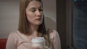 Όμορφος ελκυστικός λυπημένος νέος καφές κατανάλωσης γυναικών στον καφέ Νύχτα βραδιού Κόκκινος καναπές φλυτζανιών καφέ εγγράφου φιλμ μικρού μήκους