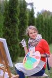 Όμορφος ζωγράφος γυναικών που θέτει και που χαμογελά, που γελά στη κάμερα Στοκ Εικόνα