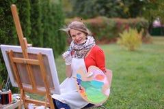 Όμορφος ζωγράφος γυναικών που θέτει και που χαμογελά, που γελά στη κάμερα Στοκ Φωτογραφίες
