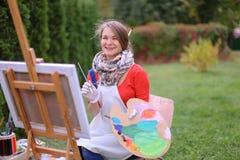 Όμορφος ζωγράφος γυναικών που θέτει και που χαμογελά, που γελά στη κάμερα Στοκ εικόνες με δικαίωμα ελεύθερης χρήσης