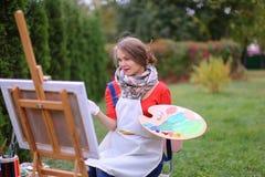 Όμορφος ζωγράφος γυναικών που θέτει και που χαμογελά, που γελά στη κάμερα Στοκ Φωτογραφία