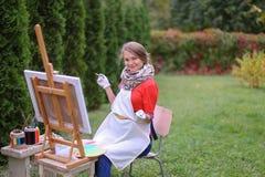 Όμορφος ζωγράφος γυναικών που θέτει και που χαμογελά, που γελά στη κάμερα Στοκ φωτογραφία με δικαίωμα ελεύθερης χρήσης