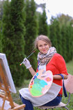 Όμορφος ζωγράφος γυναικών που θέτει και που χαμογελά, που γελά στη κάμερα Στοκ εικόνα με δικαίωμα ελεύθερης χρήσης