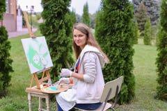 Όμορφος ζωγράφος γυναικών που θέτει και που χαμογελά, που γελά στη κάμερα Στοκ Εικόνες
